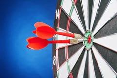 Dartboard op een blauwe achtergrond met pijlen die het centrum Ta raken Royalty-vrije Stock Afbeeldingen