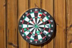 Dartboard på den wood väggen arkivfoton
