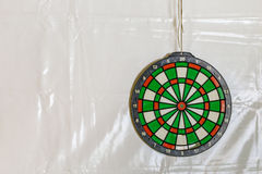 Dartboard on plastic wall. Dartboard on the wall covered by plastic tarp Stock Images