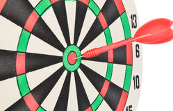 Dartboard with red dart at the center isolated on white Stock Photo