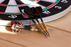 Dartboard. And six darts on wooden table Royalty Free Stock Photos
