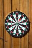 Dartboard sulla parete di legno (obiettivo di colpo del dardo) fotografia stock