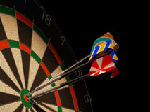 Dartboard with three darts in center target. Dartboard with three darts in center target, with multicolored generic tails Royalty Free Stock Image