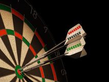Dartboard with three darts in center target. Dartboard with three darts in center target, with the types Success on tails Royalty Free Stock Image