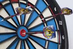 Dartboard with three darts, one hit bullseye Royalty Free Stock Photos