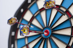 Dartboard with three darts, one hit bullseye with some selective focus. Three darts hit the dartboard, one dead center, with another one slightly away, with royalty free stock image