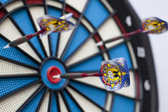Dartboard with three darts, one hit bullseye with some selective focus Stock Image