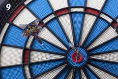 Dartboard with two darts, one hit bullseye spot on Stock Photos