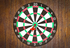 Dartboard on wood wall (Darts Hit Target) Stock Photos