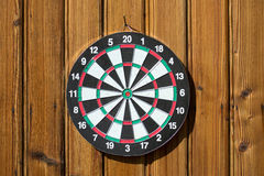 Dartboard on wood wall (no darts) Royalty Free Stock Images