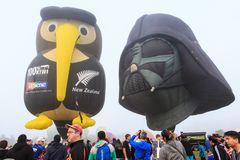 Darth Vader and kiwi shaped hot air balloons. A pair of custom made hot air balloons in the shape of Darth Vader`s helmet and `Iwi the Kiwi` hover above a crowd royalty free stock image