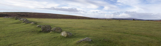 Dartmoor Panorama with boulders. Panoramic landscape view of Dartmoor looking pasdt a line of boulders towards the highest parts of the moor Stock Photo