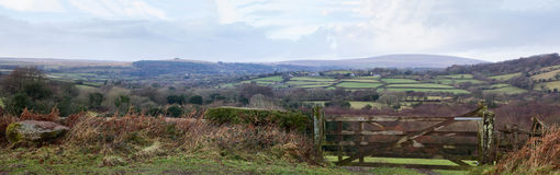 Dartmoor Panorama. Panoramic landscape view of Dartmoor looking past a lichen covered 5 bar gate, across fields with sheep and traditional farm buildings royalty free stock image