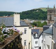 Dartmouth, Devon, Hillside Houses and Church. Picturesque view of historic houses, old church steeple, rustic wall and hilly landscape in the coastal British royalty free stock photography