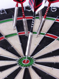 Darts 098. A close-up of steel tipped darts in a dartboard, one with a bullseye Royalty Free Stock Images