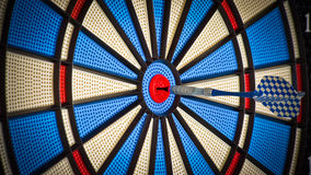 Darts. A blue darts arrow in the middle of the darts board Stock Image