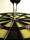 Darts. Two darts at bullseye in a dartboard Stock Images