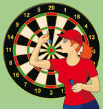 Darts. The girl playing a darts against a target for darts Stock Image