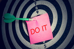 Darts arrow with pink paper note with  do it text on target center Stock Photo