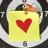Darts arrow with red heart. Darts arrow with yellow sticky note with red heart pined on target center Stock Photo