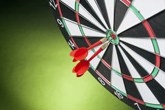 Darts arrows hitting the target center on a green background Stock Photography