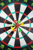 Darts arrows in the target center, closeup Stock Photo