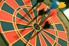 Darts arrows in the target center. Royalty Free Stock Photos