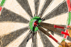 Darts board with 3 arrows in bullseye Royalty Free Stock Photos