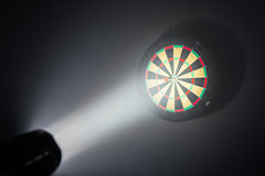 Darts board illuminated with a spotlight Royalty Free Stock Photography