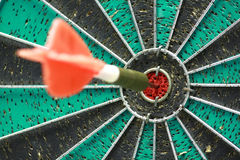 Darts board with single arrow in bullseye Stock Photography