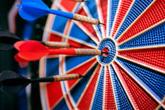 Darts in bullseye in dartboard Stock Photography