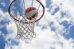 Basketball concept. Close up of ball falling into basket Royalty Free Stock Image