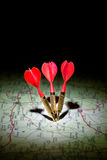 Darts on a dark map. Dark map with red darts and their shadows Stock Photos