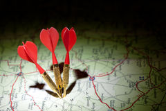 Darts in a dark roadmap. Dark map with red darts and their shadows Royalty Free Stock Photography