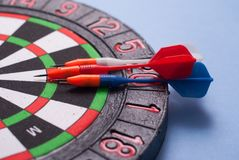 Darts and dart for throwing. On a blue background Royalty Free Stock Photos