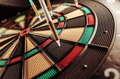 Darts in dartboard Stock Photos