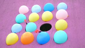 Balloons burst - prize attraction in the amusement park. Darts fly in the direction of balloons and burst them. Two darts fly past, and the next dart hits the stock footage