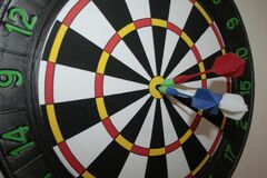 Darts game with three darts in the middle