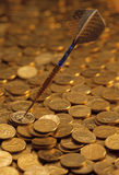 Darts on a heaped of gold coins Royalty Free Stock Image