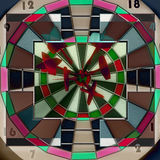 Darts hitting directly in bulls eye Royalty Free Stock Images