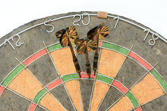 Darts hitting triple 20 square to win cricket game. On yellowed old dart board isolated on white background royalty free stock images
