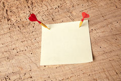 Darts in a message. Red darts in an empty or blank notepad on a vintage wooden board Royalty Free Stock Photography