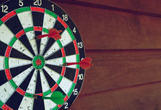Darts over wooden background. Arrows missed target Stock Image