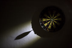 Darts. Right on target concept using dart in the bullseye on dartboard Royalty Free Stock Photos