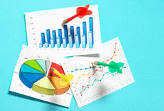 Darts sticking in graphs. Royalty Free Stock Photos