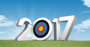 Darts target as 2017 against a composite image 3D of grassland and sky. Darts target as 2017 against a composite image 3D of grassland and blue sky Royalty Free Stock Photo