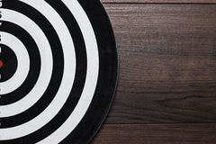 Darts target on dark wooden background Stock Images