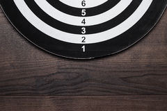 Darts target on dark wooden table Royalty Free Stock Photo