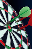 Darts in a target for darts against a dark background. Royalty Free Stock Images