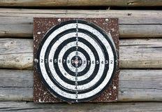 Darts target. Old darts target hanging on  wooden wall Stock Photos